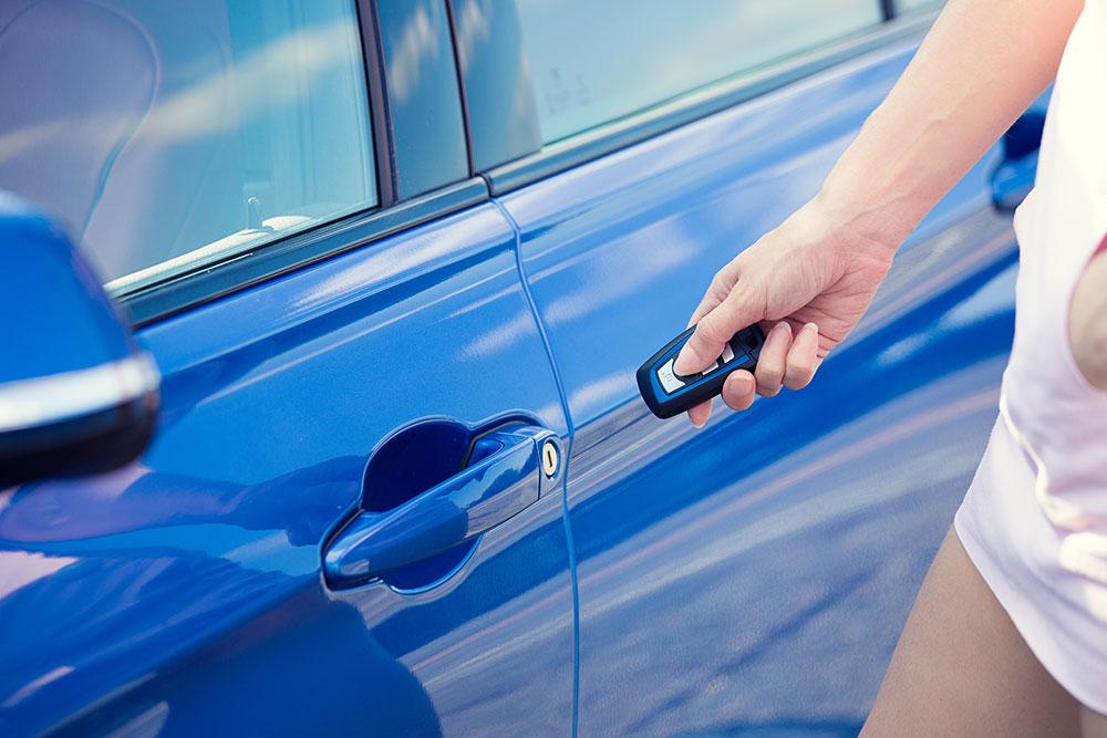Nainen seisoo auton vieressä ja paina avaimen kaukolukitusnappia