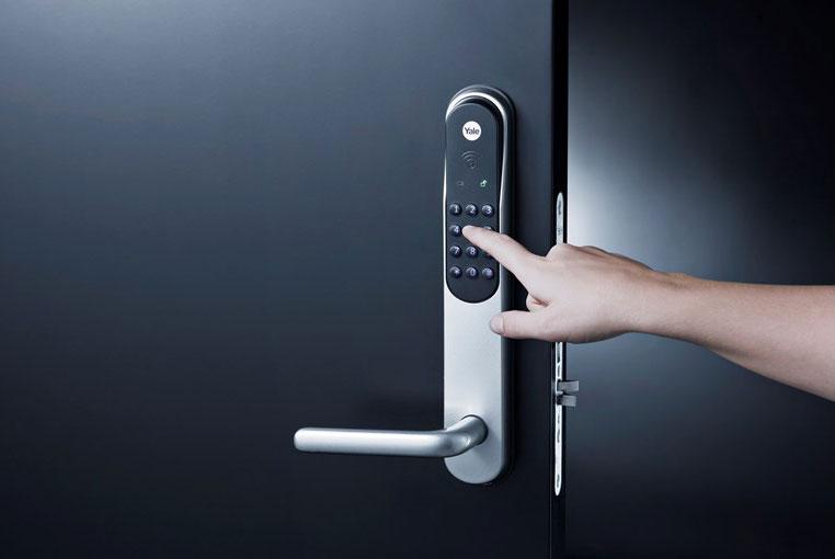 Yale Doorman -älylukko mustassa ovessa, henkilö näppäilee painikkeita