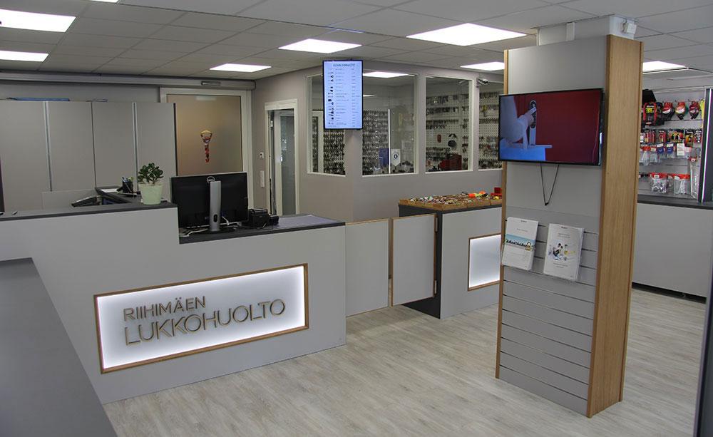 Riihimäen Lukkohuollon myymälään sisäkuva, keskellä myyntitiski, jossa on logo.